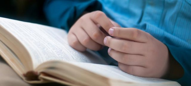 image of child's hands on a Bible